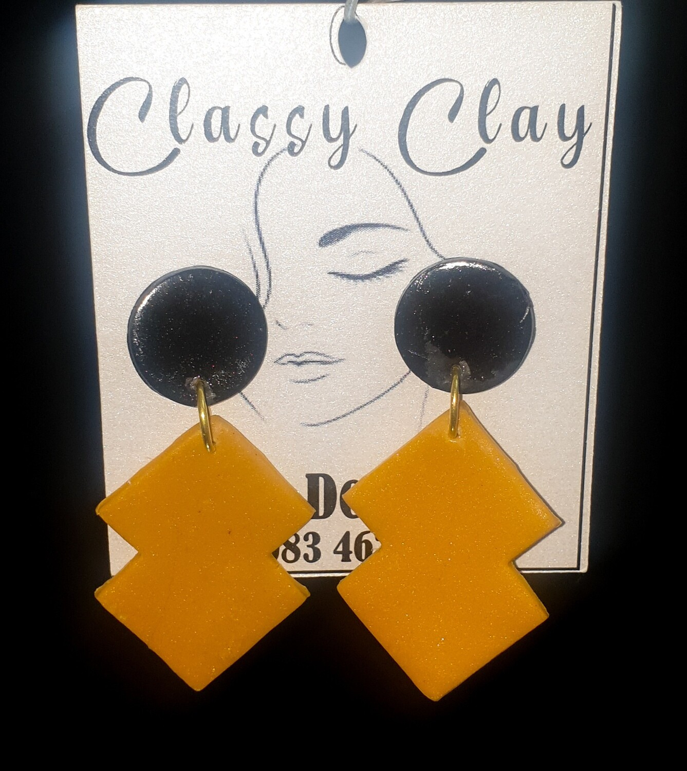 Double rectangular mustard hanging with black stud earrings