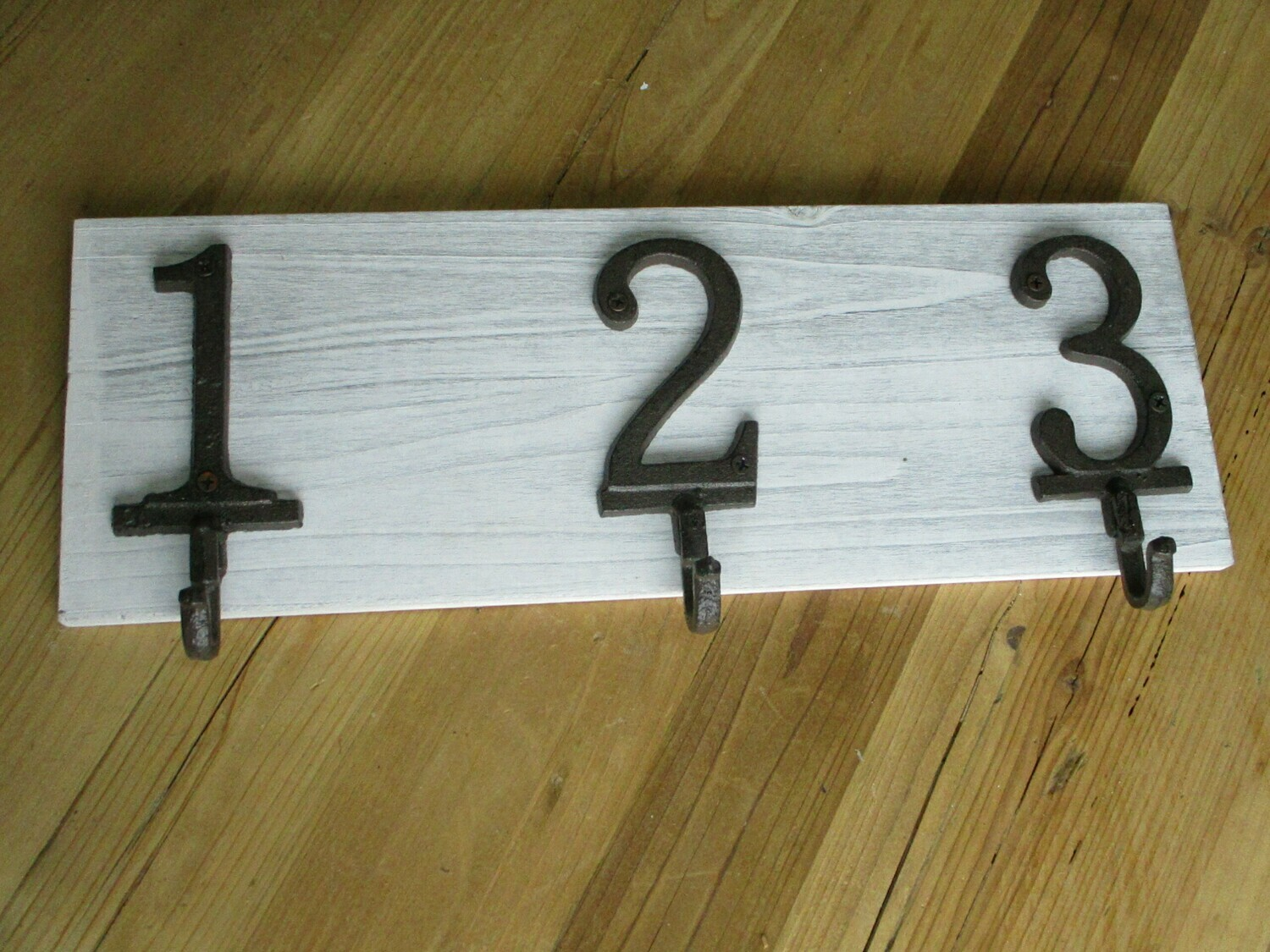 CAST IRON NUMBERS 1,2,3 COAT HOOKS ON DISTRESSED WOOD BACKING