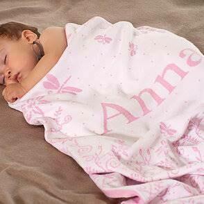 Babyfilt med blommor och barnets namn. 75 cm x 100 cm. Rosa