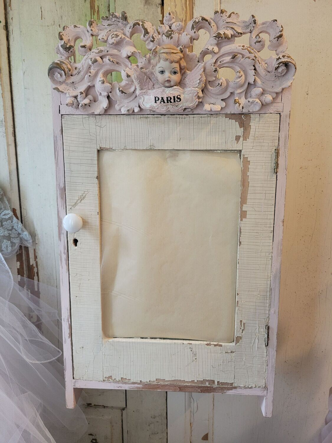 Vintage wood cabinet with mirrored door, detailed with ornate header and antique angel
