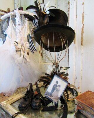 Antique black top hat on hat rack with antique postcard