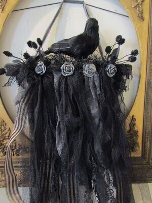 Halloween black crow perched on a branch with ornate garland wall or door decoration