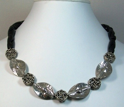 Necklace of sterling silver leaves separated by filigree silver beads , finished with twisted black stone beads
