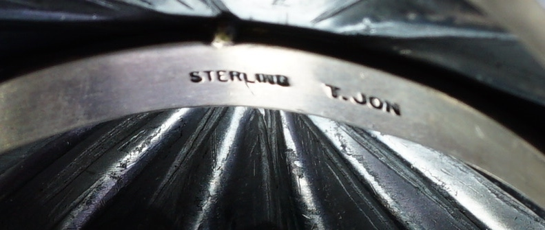 A close-up image of the artist's signature of authenticity on the back of the sterling silver stamped bracelet