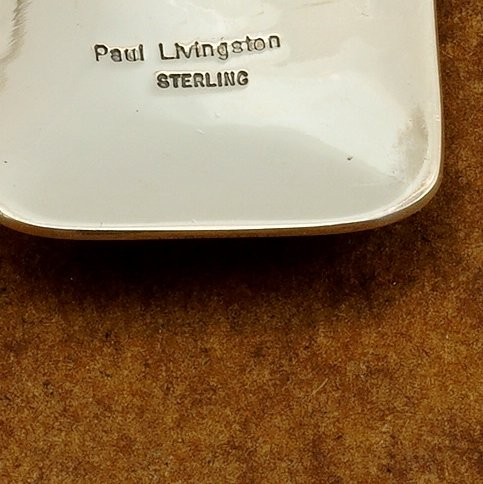 A picture of the back of the pendant with Paul Livingston's signature