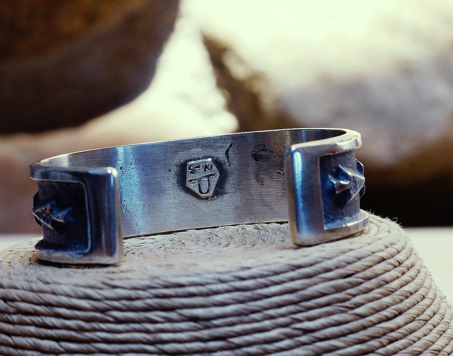 Image of the sterling silver back of the arrow overlay bracelet with the artist's engraving