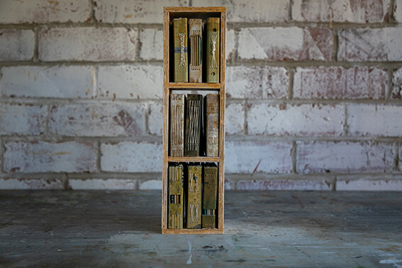 A collection of small books with handmade shelf #1